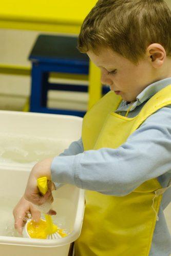 Child cleaning dish at Divinum Auxilium Academy